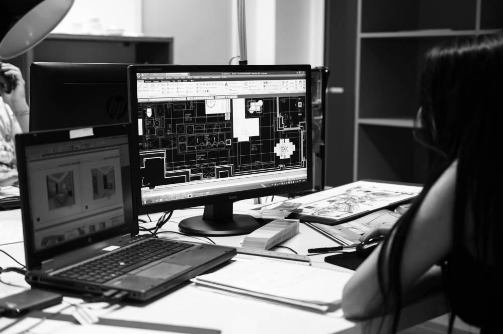 photo en noir et blanc d'une architecte à son burau en train de travailler sur ordinateur