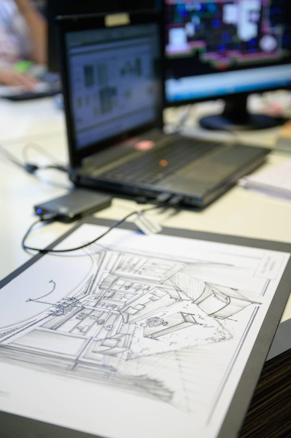 photo d'un bureau d'architecte montrant un ordinateur et un plan dessiné prise par photographe entreprise et corporate