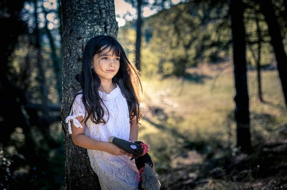 Portrait d'une fillette contre un arbre, elle tient un doudou dans la main. Photo prise par la photographe Florence Martin