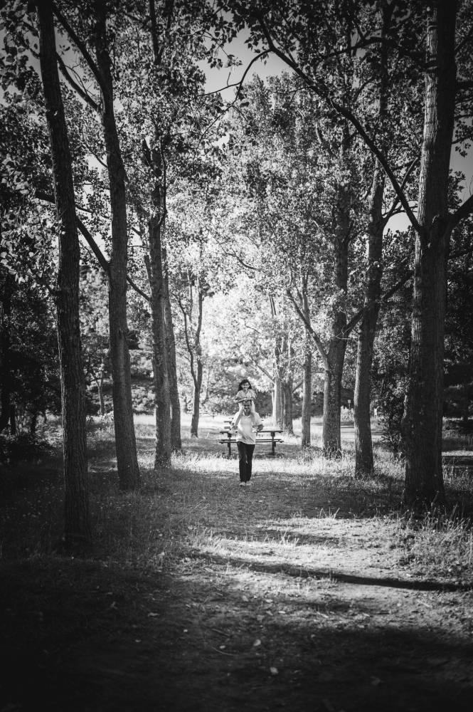 Photo en noir & blanc d'une père qui porte sa fille sur les épaules dans la forêt prise par Florence Martin photographe professionnelle dans le Var et les Alpes Maritimes