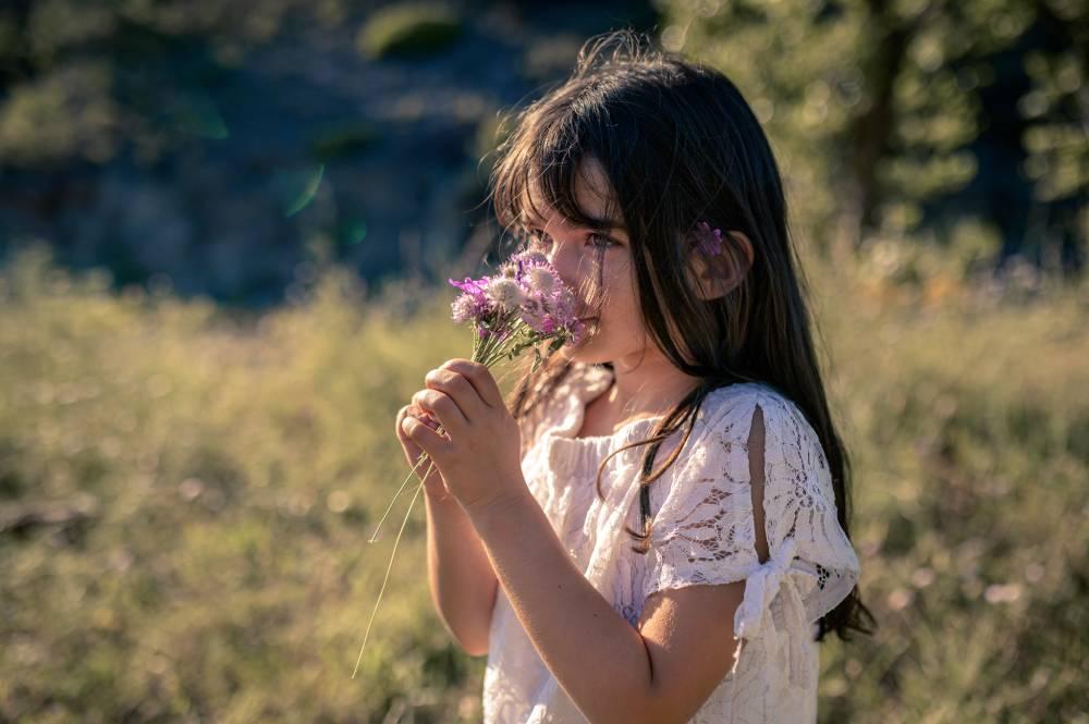 photo d'une fillette qui sens un bouquet de fleurs des champs prise par Florence Martin photographe professionnelle dans le Var et les Alpes Maritimes