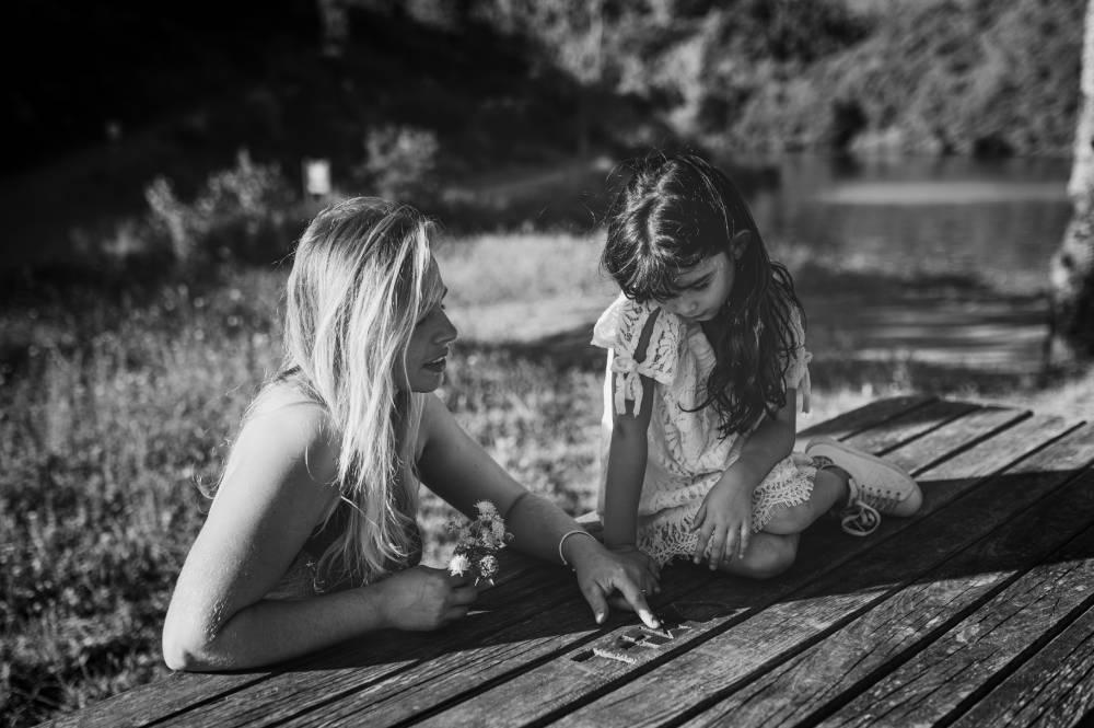 Photo d'une maman et sa fille assis sur une table en bois à coté d'un plan d'eau prise par Florence Martin photographe professionnelle dans le Var et les Alpes Maritimes