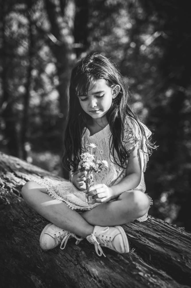 Photo de fillette tenant des fleurs dans la main assis sur un tronc d'arbre prise par Florence Martin photographe professionnelle dans le Var et les Alpes Maritimes
