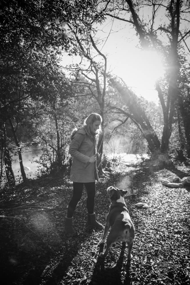 Photo en noir & blanc d'un femme qui joue avec son chien dans la forêt prise par Florence Martin photographe professionnelle dans le Var et les Alpes Maritimes