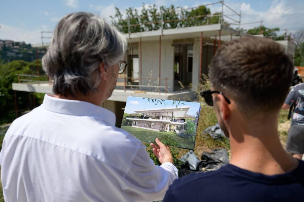 2 hommes regardent une maison en construction en comparant la maison avec un image d'architecte, photo prise par Florence Martin photographe professionnelle dans le Var et les Alpes Maritimes