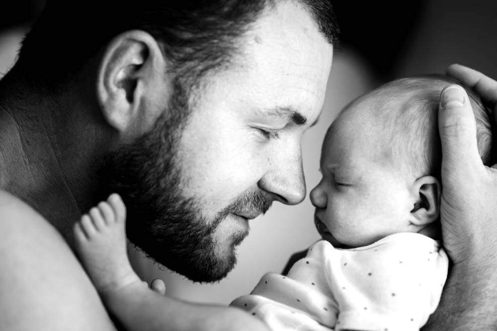 Photo d'un père qui tient son bébé dans la main prise par Florence Martin photographe professionnelle dans le Var et les Alpes Maritimes
