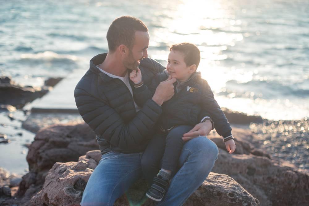 Photo d'un père avec son fils assis sur un rocher devant la mer prise par Florence Martin photographe professionnelle dans le Var et les Alpes Maritimes