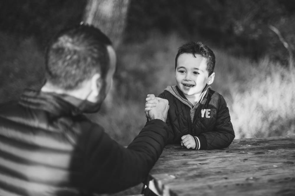Photo d'un père avec son petit garçon qui font un bras de fer prise par Florence Martin photographe professionnelle dans le Var et les Alpes Maritimes
