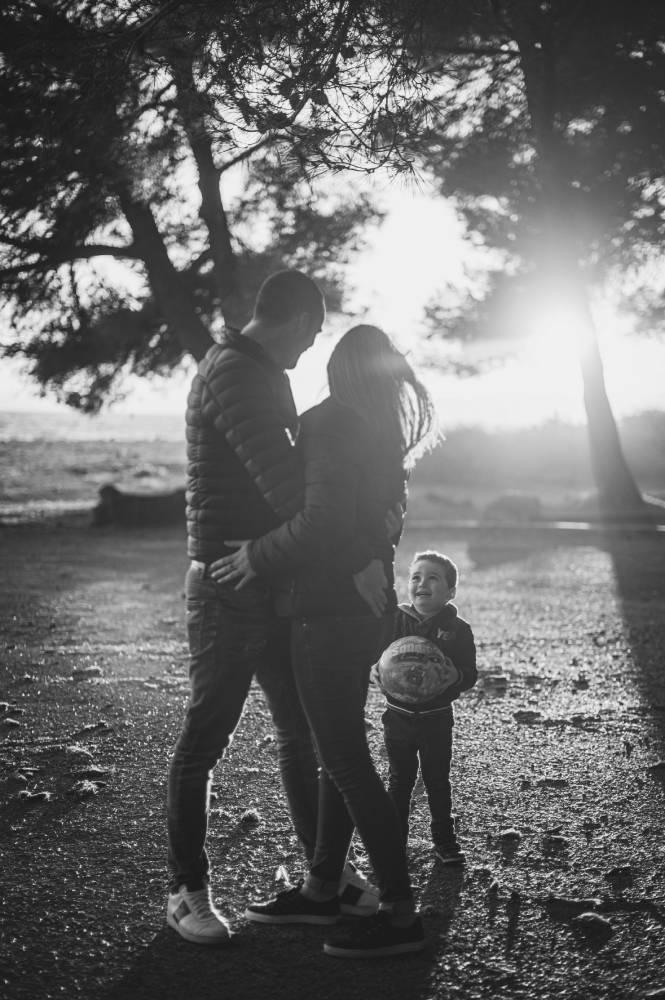 Photo en noir & blanc de parents avec leur petit garçon qui tient un ballon dans la main prise par Florence Martin photographe professionnelle dans le Var et les Alpes Maritimes