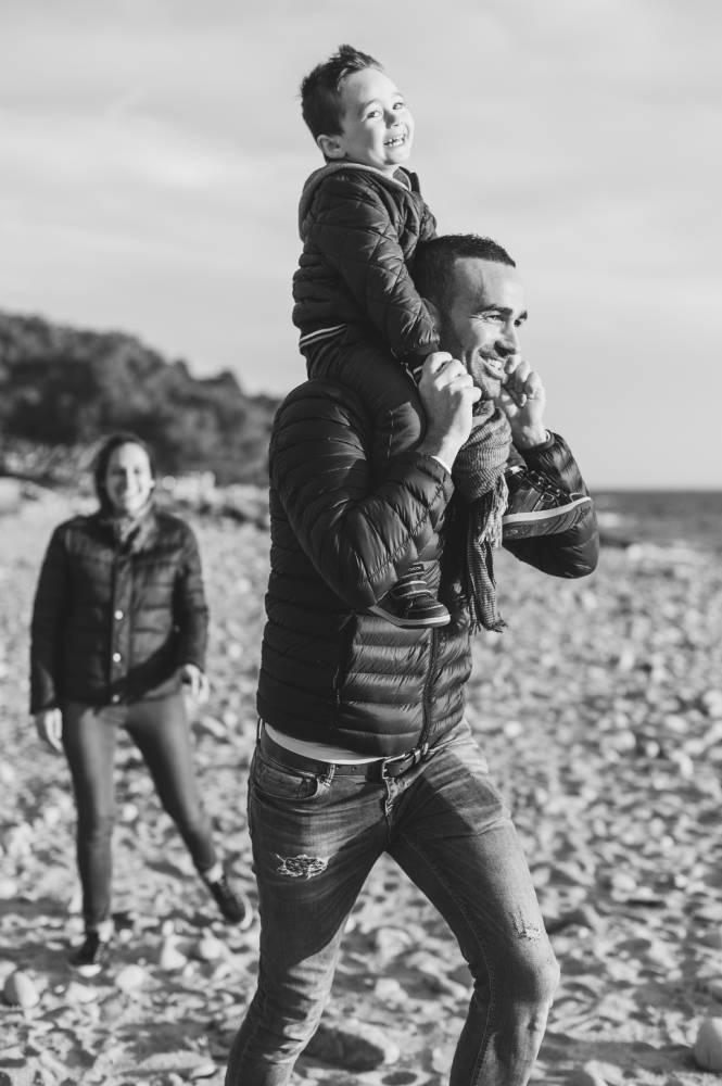 Photo d'un père qui porte son fils sur les épaules, on voit la mère derrière prise par Florence Martin photographe professionnelle dans le Var et les Alpes Maritimes