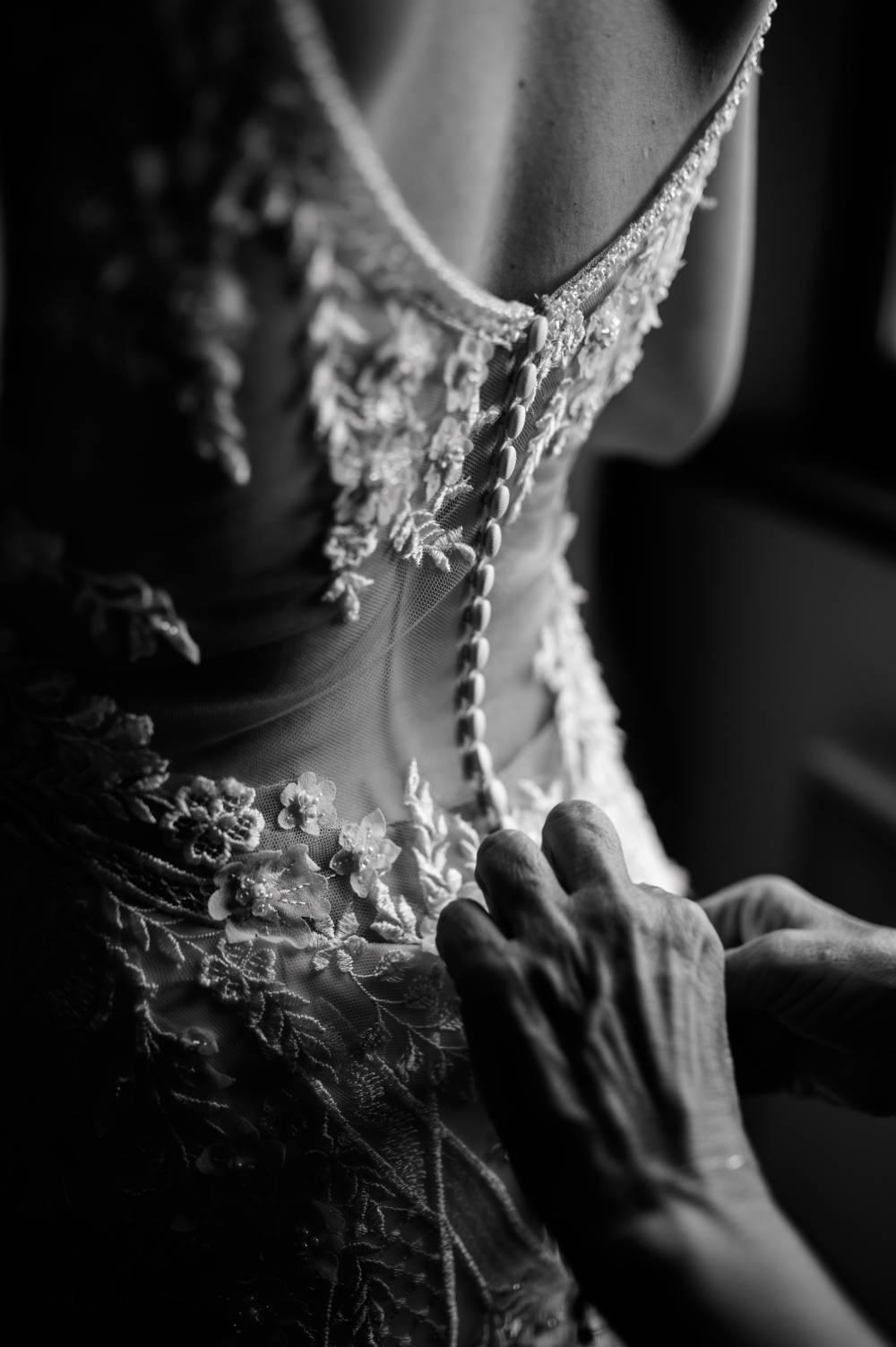 dos de la mariée, des main boutonnent la robe de mariée, photo prise par photographe de mariage Alpes maritimes