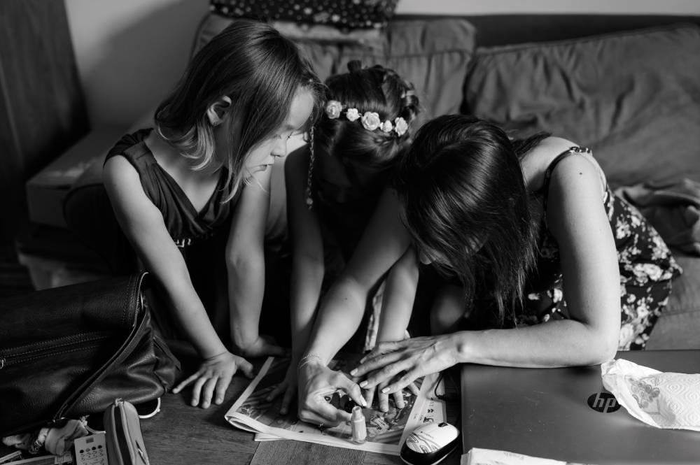 photo en noir et blanc de 2 enfants qui se font peindre les ongles à un mariage. Photo prise par la photographe Florence Martin.
