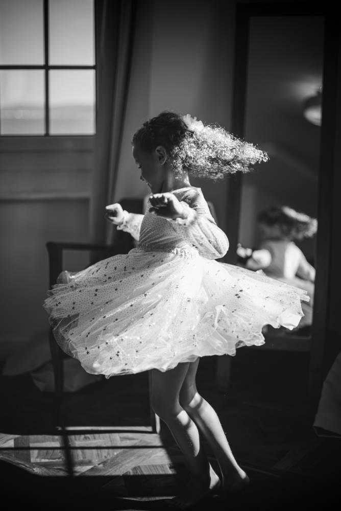 photo en noir et blanc d'une fillette qui danse dans une robe blanche. Photo prise par la photographe Florence Martin.