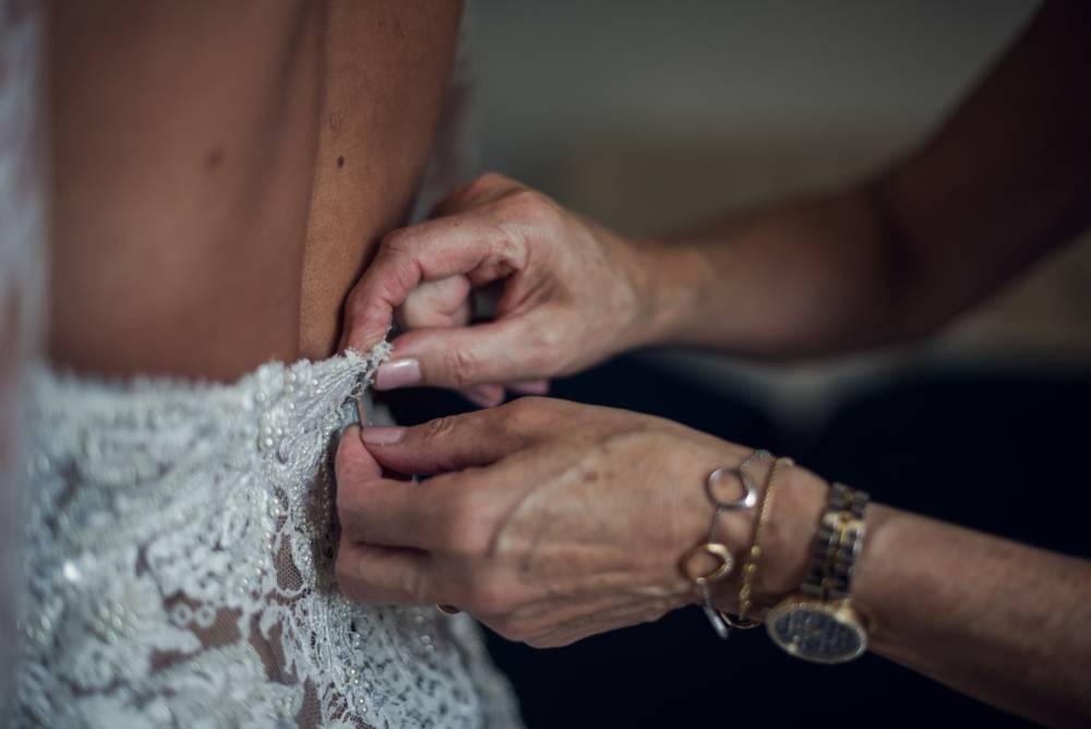 Photo d'une partie du dos de la marié avec des main de quelqu'un qui ferme sa robe. Photo prise par la photographe Florence Martin.