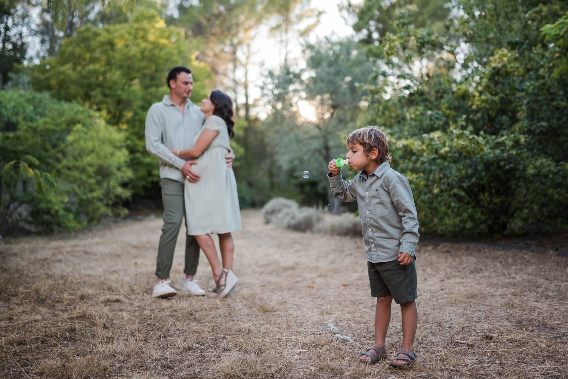 Photo d'une famille, père, mère enceinte avec leur fils prise par photographe famille & maternité