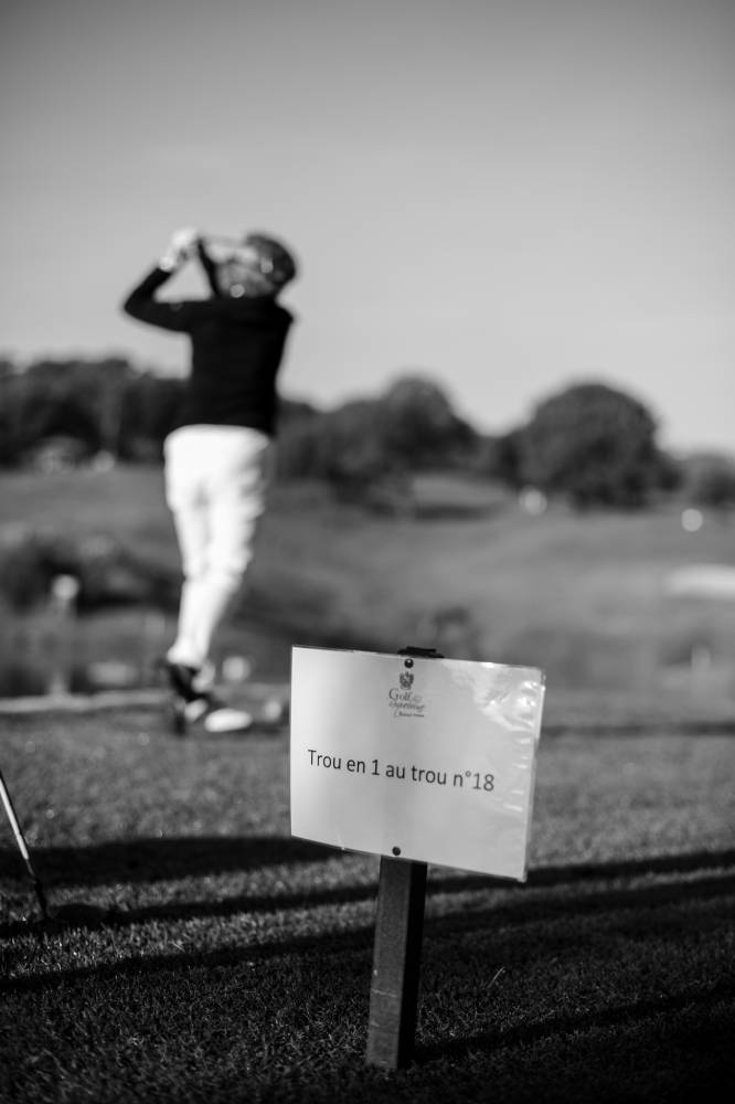 Golfeuse qui a vient de frappé la balle flou car le focus est sur le petit panneau. photo d'entreprise prise par Florence Martin, photographe professionnelle dans le Var et les Alpes Maritimes