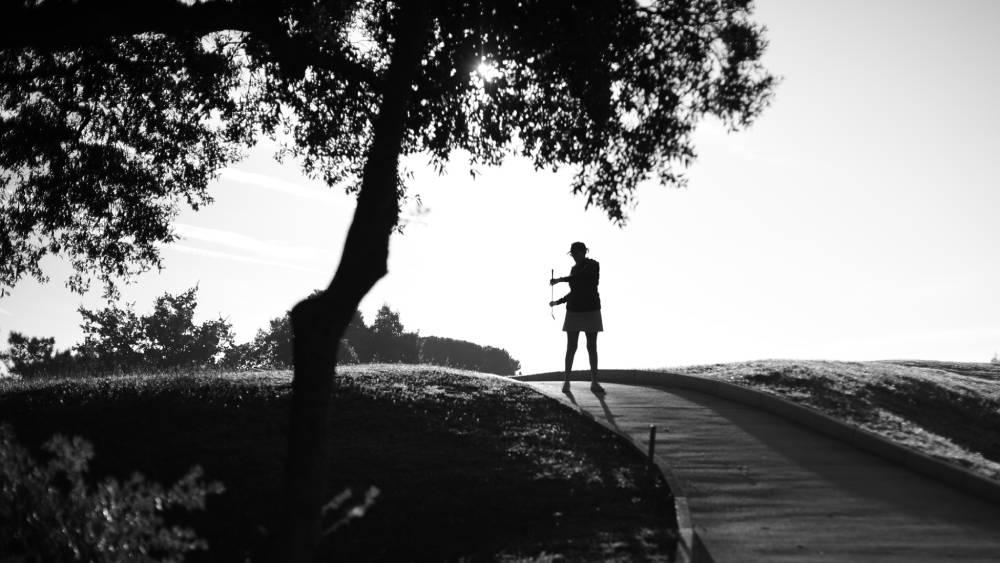 Photo noir & blanc d'entreprise montrant une golfeuse en contrejour ensolleillé, photo prise par Florence Martin, photographe professionnelle dans le Var et les Alpes Maritimes