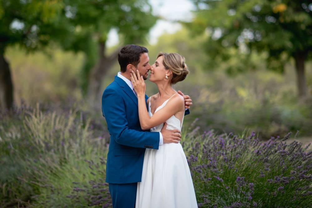 Les mariés s'embrassent dans un champs de lavande