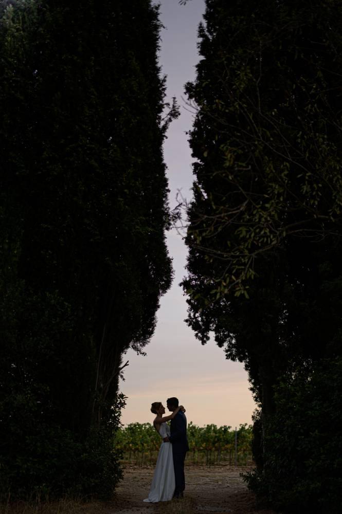 Les mariés s'entrelacent au crépuscule entre deux arbres, photo prise par Florence Martin, photographe de mariage dans le Var et les Alpes Maritimes