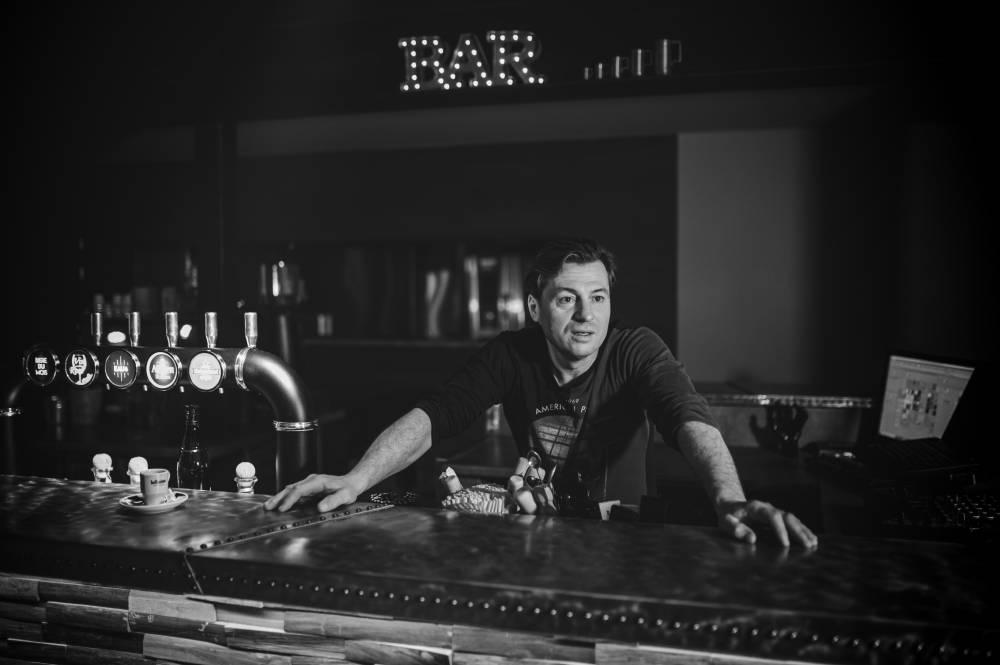 le patron d'un bar derrière le comptoir, photo d'entreprise prise par Florence Martin, photographe professionnelle dans le Var et les Alpes Maritimes